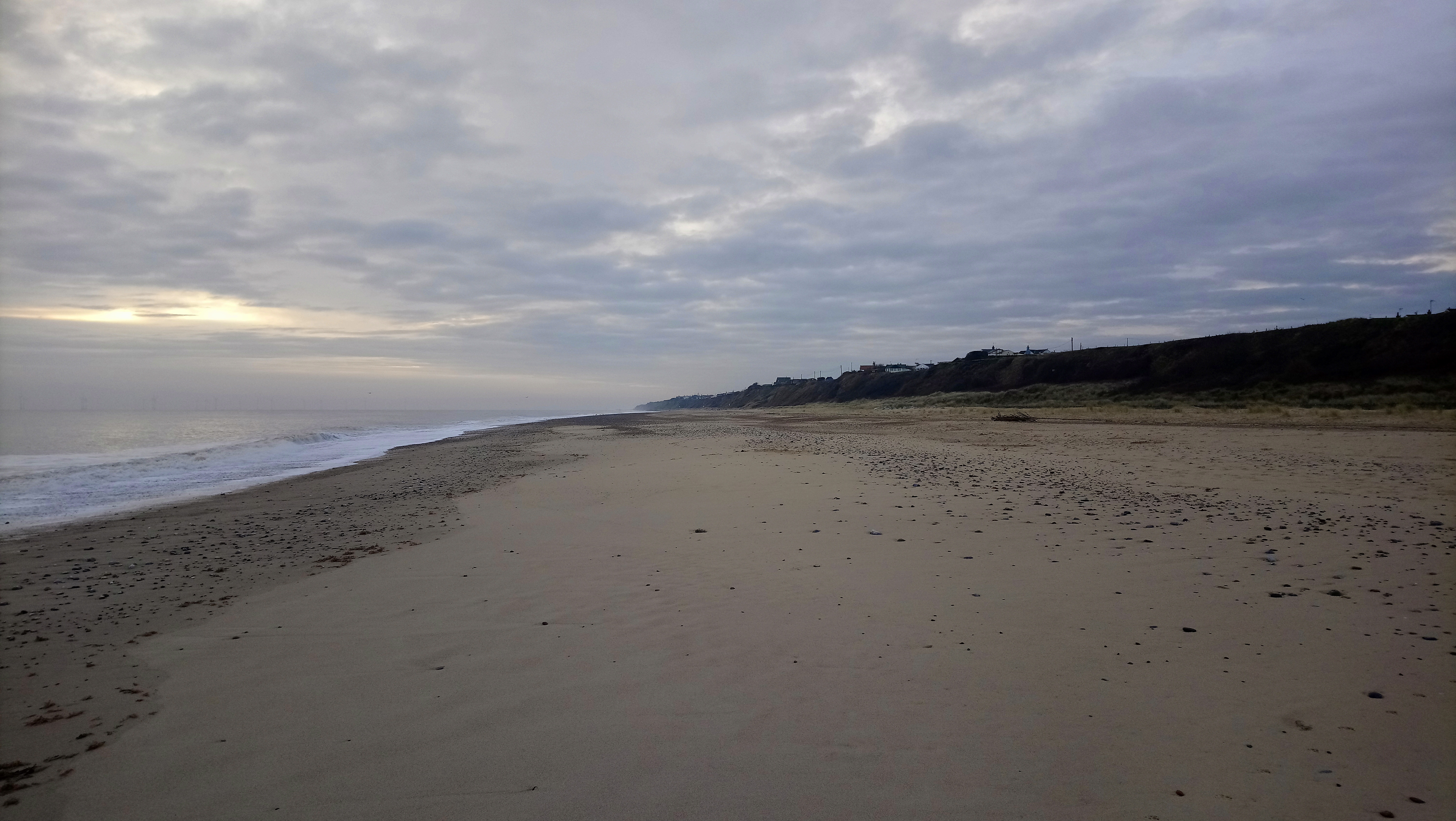 a photo of a sandy beach that stretches into the distance