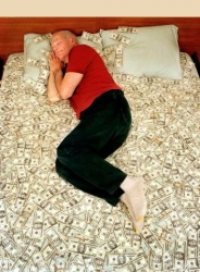 man sleeps on a bed of bank notes across the bed