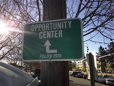 "picture of a sign with the words ""opportunity Centre"" displayed on it and an arrow pointing forward towards it"